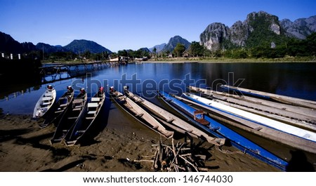 River in Laos.Vang Vieng Landscape.Boat park at riverside.wood bridge across river. sky is dark blue at evening. - stock photo