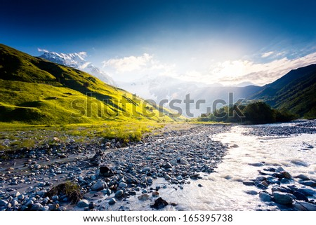 River in mountain valley at the foot of Tetnuldi glacier. Upper Svaneti, Georgia, Europe. Caucasus mountains. Beauty world. - stock photo