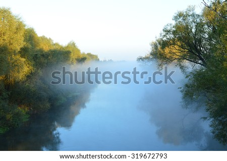 River in the fog/river in the early morning mist in autumn