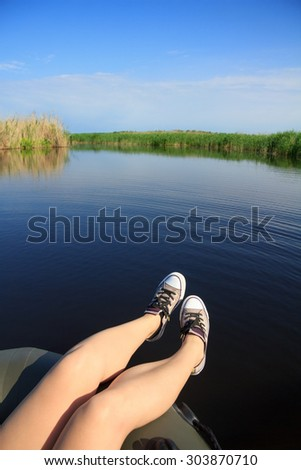 River landscape, clouds in the blue sky, the girl's legs in sneakers, river, green tourism, travel along the river, boating, summer sunny day, aboard an inflatable boat, aquatic vegetation. - stock photo