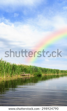 River landscape, rainbow in the blue sky, the waves on the water, river, green tourism, travel along the river, boating, summer sunny day after the storm, a harbor for ships, aquatic vegetation. - stock photo
