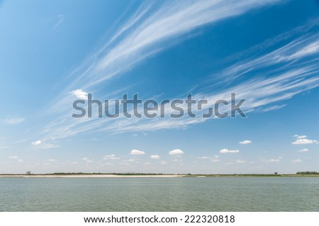 River  landscape with clouds and blue sky in summer - stock photo