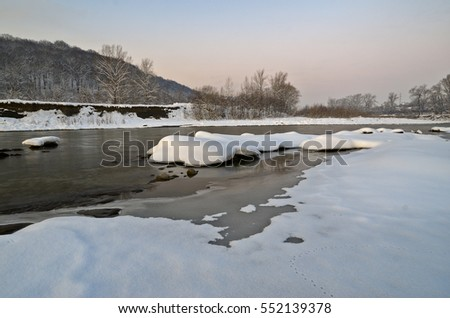 River landscape with rocks in the foreground. The evening, after sunset. Caucasus, Russia