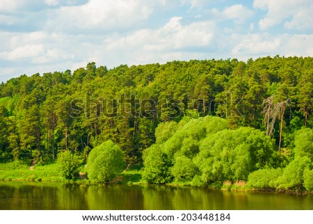 River lune landscape. Green trees and clouds in blue sky.
