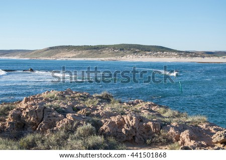 River mouth where the Indian Ocean meets the Murchison river with rocky riverbank, boat and coastal dunes in Kalbarri, Western Australia/Boating through the River Mouth/Kalbarri, Western Australia - stock photo