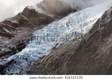 River of ice - glacier in Himalayas, Nepal. Beautiful landscape of a white snowy mountain glacier coming down between two rocky slopes in fog and clouds. Mountain glacier background. - stock photo