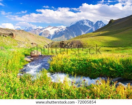 River on meadow in mountain valley. Natural composition - stock photo
