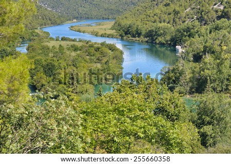 River passing through a lush forest with a boat  - stock photo