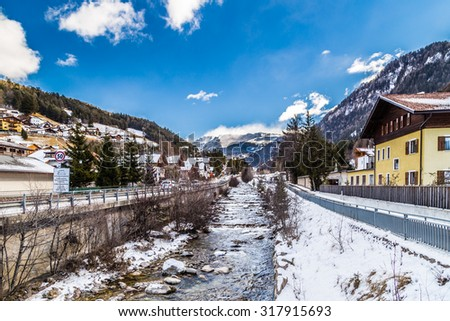 River passing through snowy alpine village in Italy illuminated by sun with mountains in the background