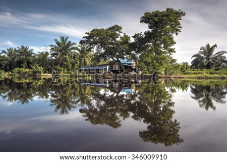 River reflection during daytime with rural house and tree. - stock photo