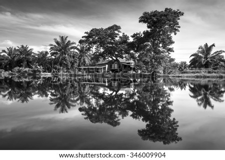 River reflection during daytime with rural house and tree in black and white format - stock photo