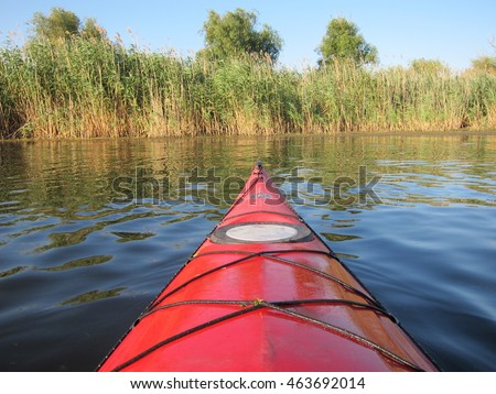 RIVER REPIDA, ODESSA REGION, UKRAINE - JULY 16, 2016: Nose of a red kayak moving quietly through a calm surface of the water