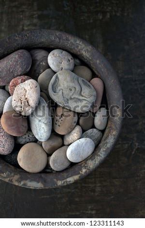 River stones collected in a rust bowl.