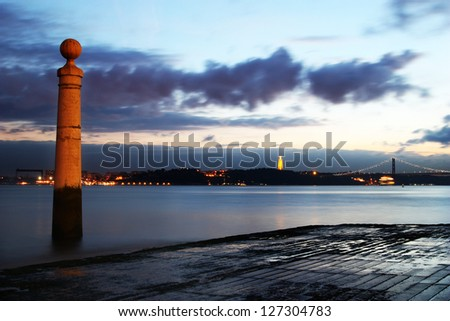 River view from the beach at sunset. City lights on other margin and bridge