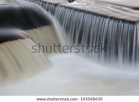 river water cascading over a weir on the river calder in west yorkshire
