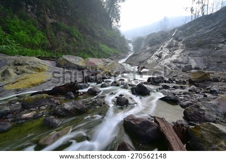 River water green with volcanic sulphur content flowing in East Java, Indonesia - stock photo