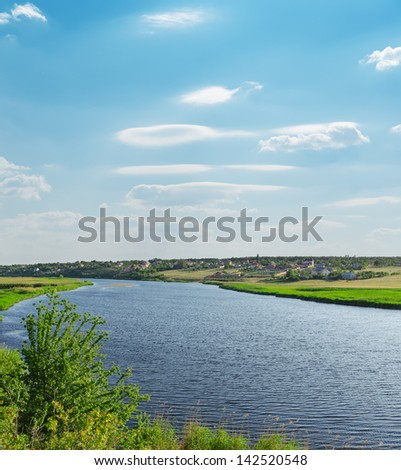 river with green riverside and light cloudy sky - stock photo