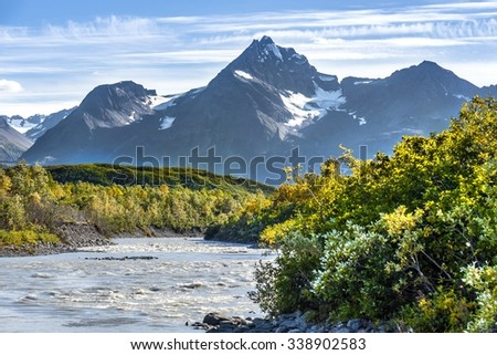 river with partially snowy mountains in background Valdez - Alaska