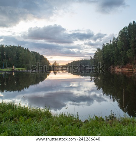 river with reflections in water and sandstone cliffs in latvia - square image - stock photo