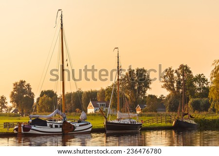 River with sailing boats in the Dutch province of Friesland during sunset - stock photo