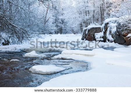 River with snow and ice in the winter woods - stock photo