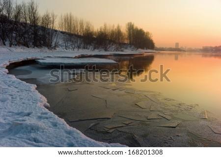riverbank covered snegomv light of the setting sun - stock photo