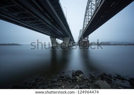 Riverbank. Two parallel bridges shot on long exposure - stock photo