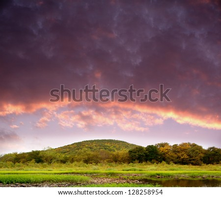 Riverbank with clouds. - stock photo
