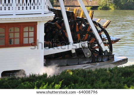 Riverboat is docked waiting for it's next passengers. Steam is seen coming from the power-plants that turn the paddles at the stern of the  ship. - stock photo