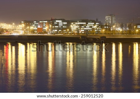riverside at night with illuminated office buildings