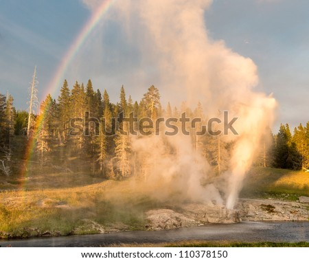 Riverside Geyser erupting at twilight in Yellowstone National Park, Wyoming - stock photo