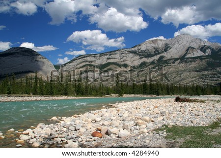 Riverside landscape - River, hills, blue sky and white clouds - stock photo