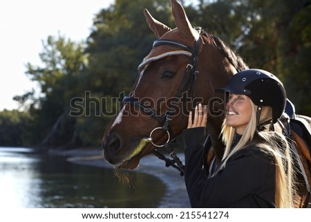 Riverside portrait of happy female rider and beautiful horse. - stock photo
