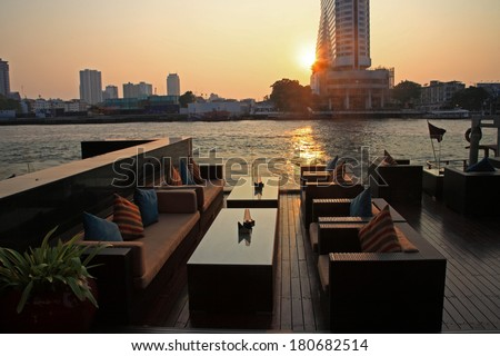 riverside restaurant seats and tables near Chao phraya river during sunset in Bangkok, Thailand - stock photo