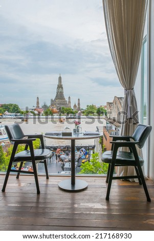 Riverside seats and tables near Chao phraya river in Bangkok, Thailand - stock photo