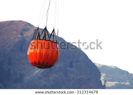 Riverside, WA, USA August 18, 2015: A helicopter-drawn water bucket lifts off after re-filling in the Okanogan River and heads off to fight the Okanogan Complex Fire, WA state's largest fire ever - stock photo