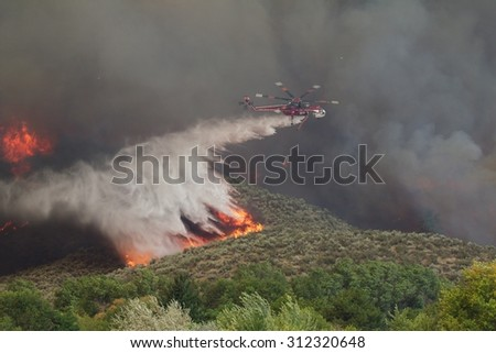Riverside, WA, USA August 18, 2015: A helicopter dumps hundreds of gallons of water to extinguish flames on the Okanogan Complex Wild Fire, Washington state's largest, most destructive fire ever - stock photo