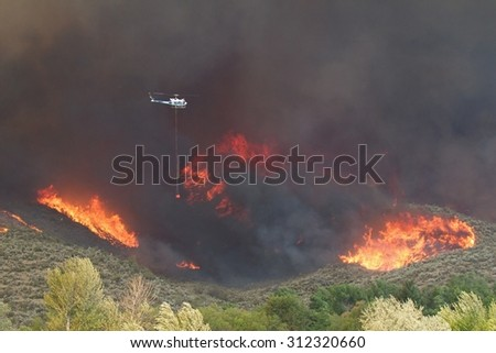 Riverside, WA, USA August 18, 2015: A helicopter finds its way thru smoke and flames as it helps to fight the Okanogan Complex Fire, the largest, most destructive fire in Washington State history  - stock photo