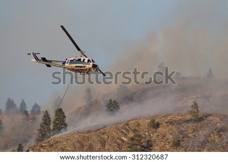 Riverside, WA, USA August 18, 2015: Okanogan Complex Wild Fire.  A helicopter is used to help fight the fire on this steep rocky mountainside, in the Tunk Block portion of the fire