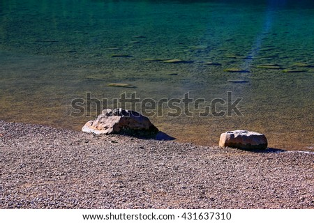 Riverside with pebbly beachside and two bigger rocks. The water has has a turquoise color. It is cold and very clear, so you can see further rocks in it. - stock photo