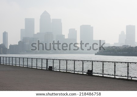 Riverwalk in London as morning haze  cuts visibility over Canary Wharf with copyspace - stock photo