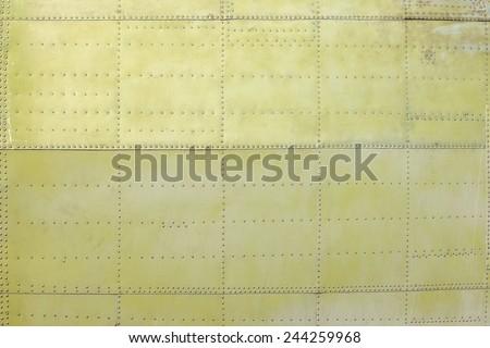 riveted khaki fuselage of light aircraft closeup - stock photo