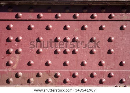 rivets in a red steel plate