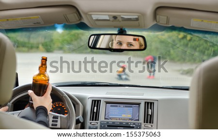 Road accident due to alcohol about to happen as a drunk female driver clutching her bottle of booze in one hand while driving approaches young children playing in the road
