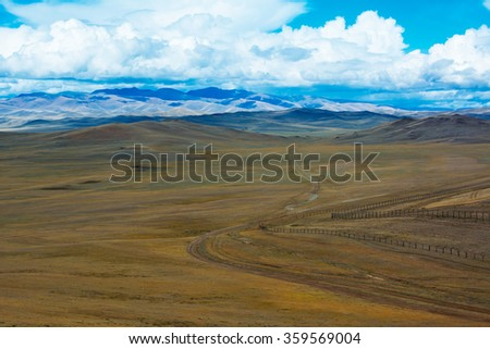 Road across the steppe, blue sky with clouds. Chuya Steppe, Siberian Altai Mountains. Steppe landscape. Summer steppe. Beautiful landscape. Steppe. Summer landscape. Mountain. Mountains. Blue sky