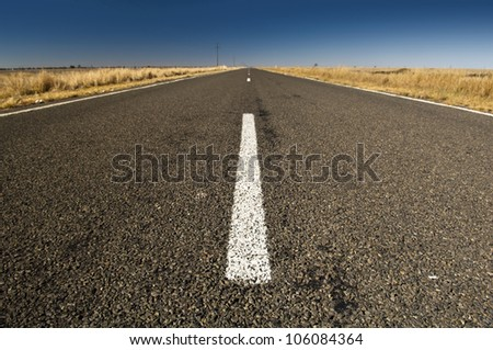 Road ahead on a wide country asphalt road with blue sky - stock photo