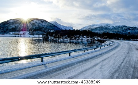 Road along seaside against sun in norway, winter - stock photo