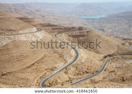Road, amazing road holiday, road trip of View of Wadi Araba on the Petra, Jordan with unusual road desert. Curve road around a mountain top in Jordan. Nobody on the curve road, or empty road, road   - stock photo