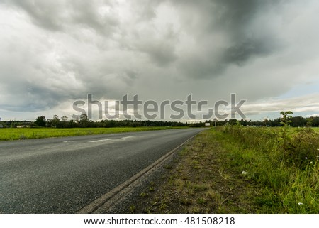Road among fields. Sunny summer landscape. Beautiful massive clouds. Stormy clouds.