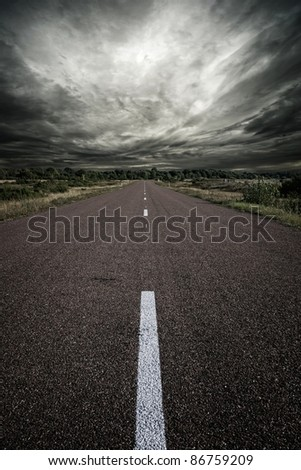 Road and a stormy sky. - stock photo
